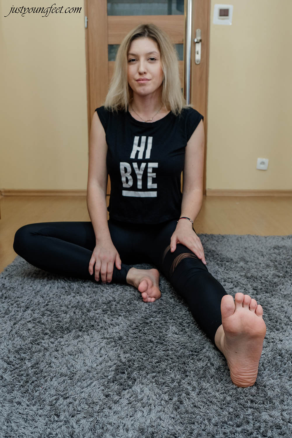 Beautiful girl in black clothes shows the soles of her